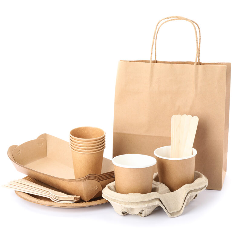 Eco - friendly tableware and paper bag isolated on white backgro